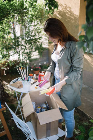 Female painter holding paint tubes over box with paint accessories. Woman getting paint tubes from box while standing in backyard.