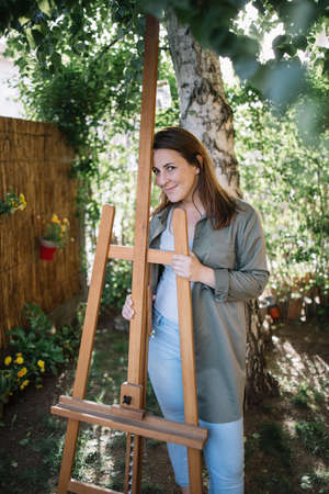 Happy woman artist standing in garden with wooden tripod. Smiling female painter posing with wooden tripod while standing in backyard.