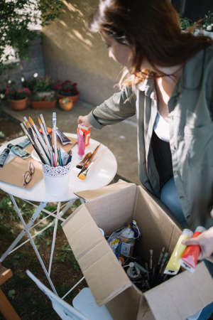 Brunette woman taking paint tubes from paper box. Woman painter picking colorful paint tubes from box while standing in backyard.
