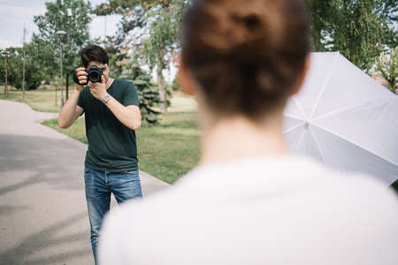 Young photographer taking photos of woman in park. Male photographer looking through camera viewfinder behind blurred woman and taking pictures.