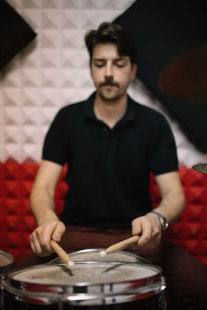 Portrait of man playing on drum set in studio. Blurred drummer holding sticks and playing instrumental music indoor.