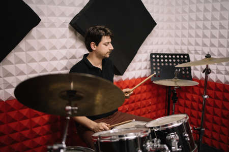 Young male drummer playing drums and cymbals. Handsome man with moustache playing with drumsticks while sitting at drums in studio.