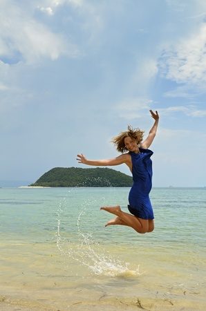 Frozen jump that reveals fun, joy and excitement  A beutiful Latvian girl is playing and enjoying this tropical paradise beach in the island of Koh Phangan, Thailand  photo