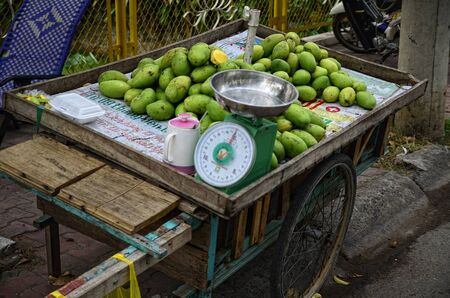 dozens: Walking the streets of Vietnam will not allow you to escape of dozens of street stands  Buy fresh mago and have a tasty snack  Stock Photo