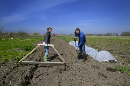 Latvian and Spanish couple working in a farm in the Latvian countryside with basic tools. photo