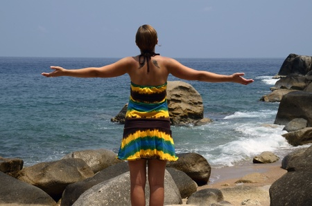 Back shape of caucasian girl relaxed with open arms on the rocks Stock Photo - 13553817