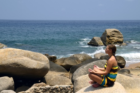 Girl meditating and practicing yoga on the rocks, with the sound of the waves photo