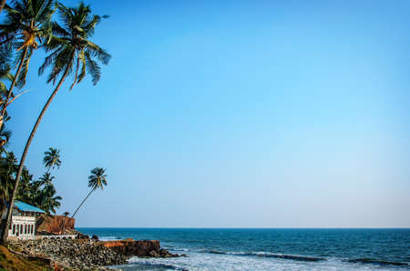 Tropical Indian village with coconut palm trees near the road and blue ocean in Varkala, Kerala, India photo