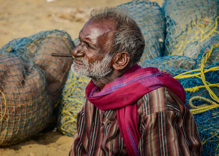 india fisherman: CHENNAI, INDIA - FEBRUARY 10, 2013: Unidentified old fisherman smoking on Marina beach in Chennai, Tamil Nadu, India