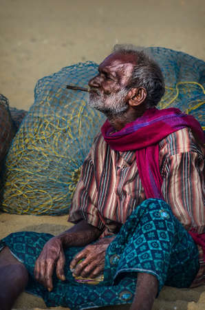 india fisherman: CHENNAI, INDIA - FEBRUARY 10, 2013: Unidentified old fisherman smoking on Marina beach in Chennai, Tamil Nadu, India