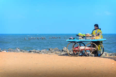 PONDICHERRY, INDIA - FEBRUARY 2, 2013: Unidentified Indian street vendor of  snacks with wheel cart on beach
