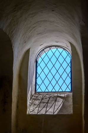 Window with a grid and blue skies in a castle photo