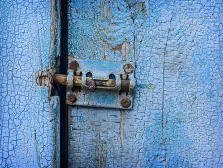 pawl: Spagnoletta sulla vecchia porta verniciata blu vicino Archivio Fotografico