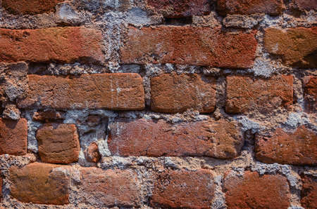 worn structure red: Red brick background: detail  close up of an old uneven brick wall. Stock Photo