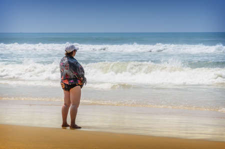 varkala: Fat lonely woman standing on the beach in Varkala, India