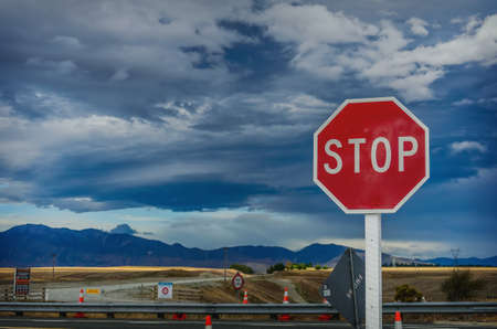 roadside red stop sign against the background of the cloudy sky and road construction photo