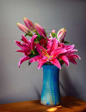 Beautiful still life with pink lilies in a blue vase photo