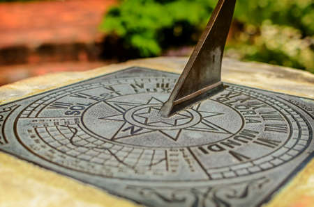 plinth: Close-up of a brass sundial mounted on a stone plinth in Wellington Botanic Garden, New Zealand Stock Photo