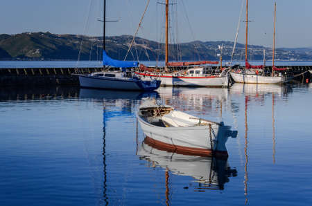 Reflections of boats in the harbor water on Pacific ocean, Wellington, New Zealand photo