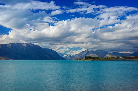 tekapo: Beautiful from The Lake Tekapo with mountains and deep blue cloudy sky. South Island, New Zealand Stock Photo