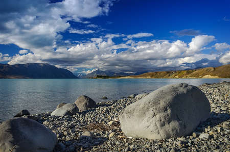 Big stones on the shore Lake Tekapo on a  mountains. South Island, New Zealand photo