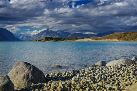 Big stones on the shore Lake Tekapo of mountains. South Island, New Zealand photo