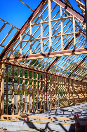 roof framework: New residential construction home framing against a blue sky