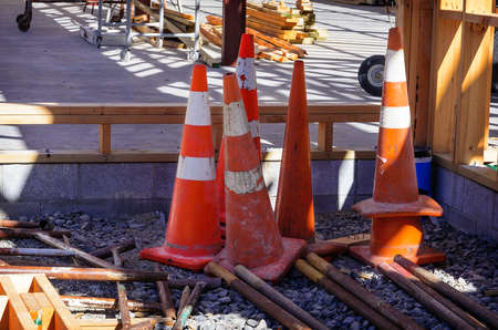 Group of old shabby traffic cones stacked and nested together. Plastic orange and white reflective safety cones with red base.
