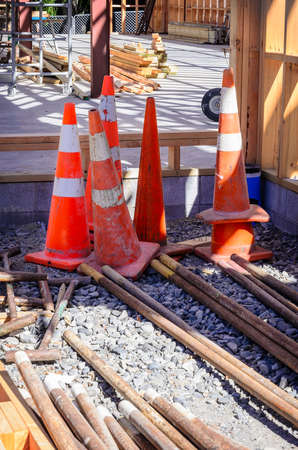 constraction: Group of old shabby traffic cones stacked and nested together. Plastic orange and white reflective safety cones with red base.
