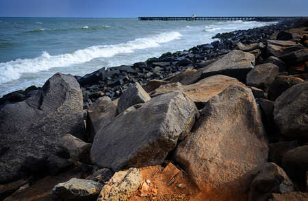 oceanside: Big stones on the oceanside against blue waves and old pier in Pondicherry, India