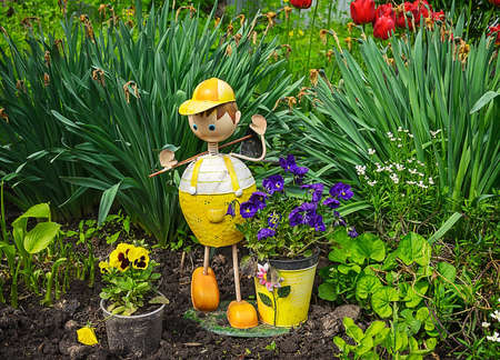 lawn gnome: Wooden garden sculpture of boy in home garden. Stock Photo