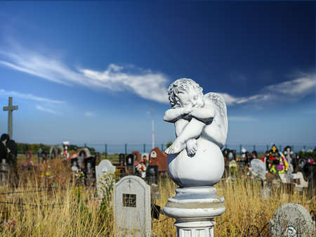 angel cemetery: Dreaming Angel on the ball at cemetery against blue sky