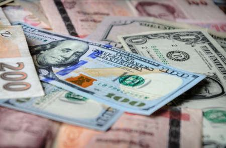 global currencies: A collection of various foreign currencies from countries spanning the globe. Many different currencies as colorful background concept global money. Soft selective focus and shallow depth of field