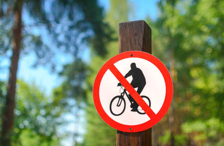 barring: Road sign circular shape with a picture of the No Cycling on a background of summer forest Stock Photo