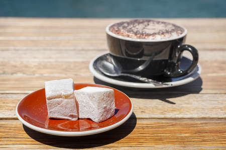 Turkish delight (lokum) confection with black tasting coffee. Soft selective focus and shallow depth of field
