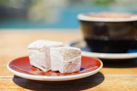 delight: Turkish delight (lokum) confection with black tasting coffee. Soft selective focus and shallow depth of field