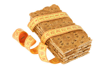 galletas integrales: Varias piezas de pan crujiente con cinta métrica aislado en blanco