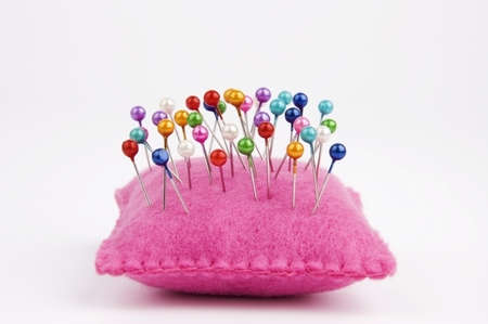 Handmade felt pin cushion with multicolored sewing pins stuck in