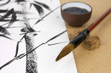 Paintbrush and ink for Chinese drawing and picture of bamboo on background Stock Photo