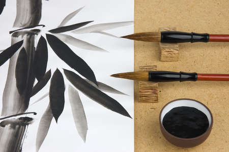 Paintbrushes and ink for Chinese drawing and picture of bamboo on background photo