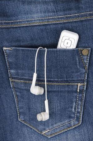 Кнопки: MP3-плеер и наушники, торчащие из кармана джинсов Фото со стока