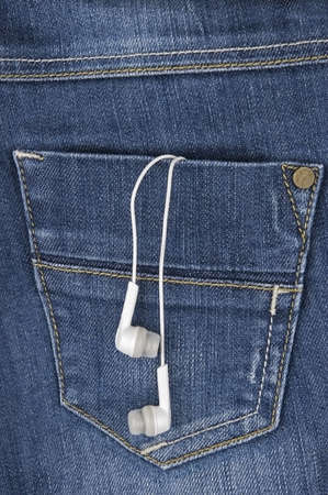 jeans pocket: Earphones hanging out of jeans pocket Stock Photo