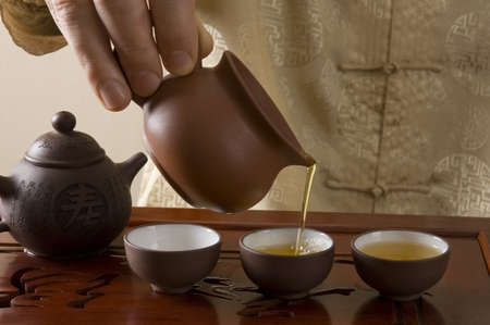 brown cup tea: Master pouring tea during traditional Chinese tea ceremony Stock Photo
