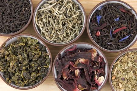 high tea: Assortment of dry tea in ceramic bowls: green, black, herbal, flower tea sorts Stock Photo