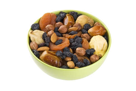 Dried fruits and nuts mixed in green bowl isolated on white photo