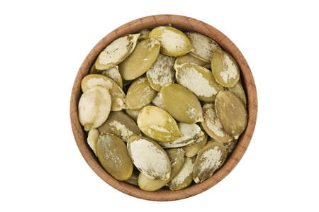 pumpkin seeds: Shelled raw pumpkin seeds in wooden bowl isolated on white