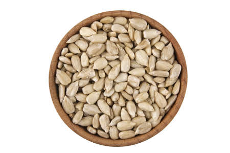 sunflower seeds: Shelled raw sunflower seeds in wooden bowl isolated on white