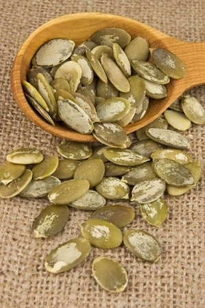 Shelled raw pumpkin seeds in wooden spoon on burlap