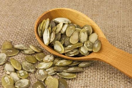 shelled: Shelled raw pumpkin seeds in wooden spoon on burlap