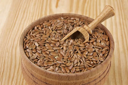 organic flax seed: Flax seeds in wooden bowl close up Stock Photo